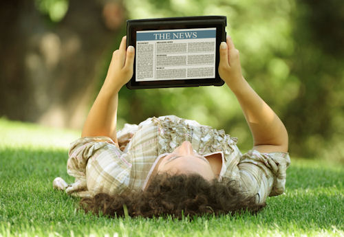 woman lying in grass reading tablet