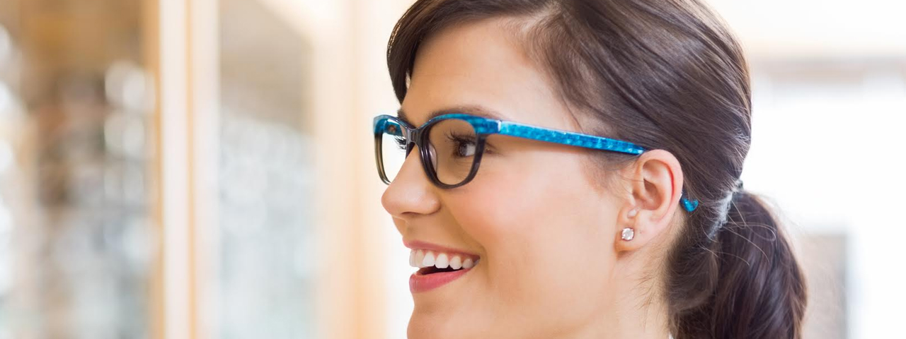 blue glasses on brunette smiling woman