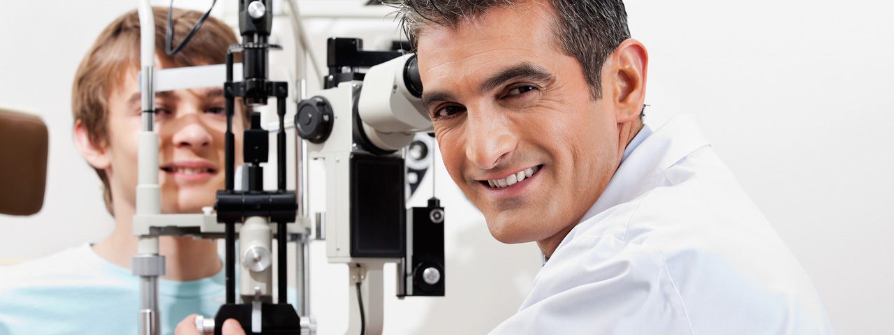 optometrist giving eye exam to boy